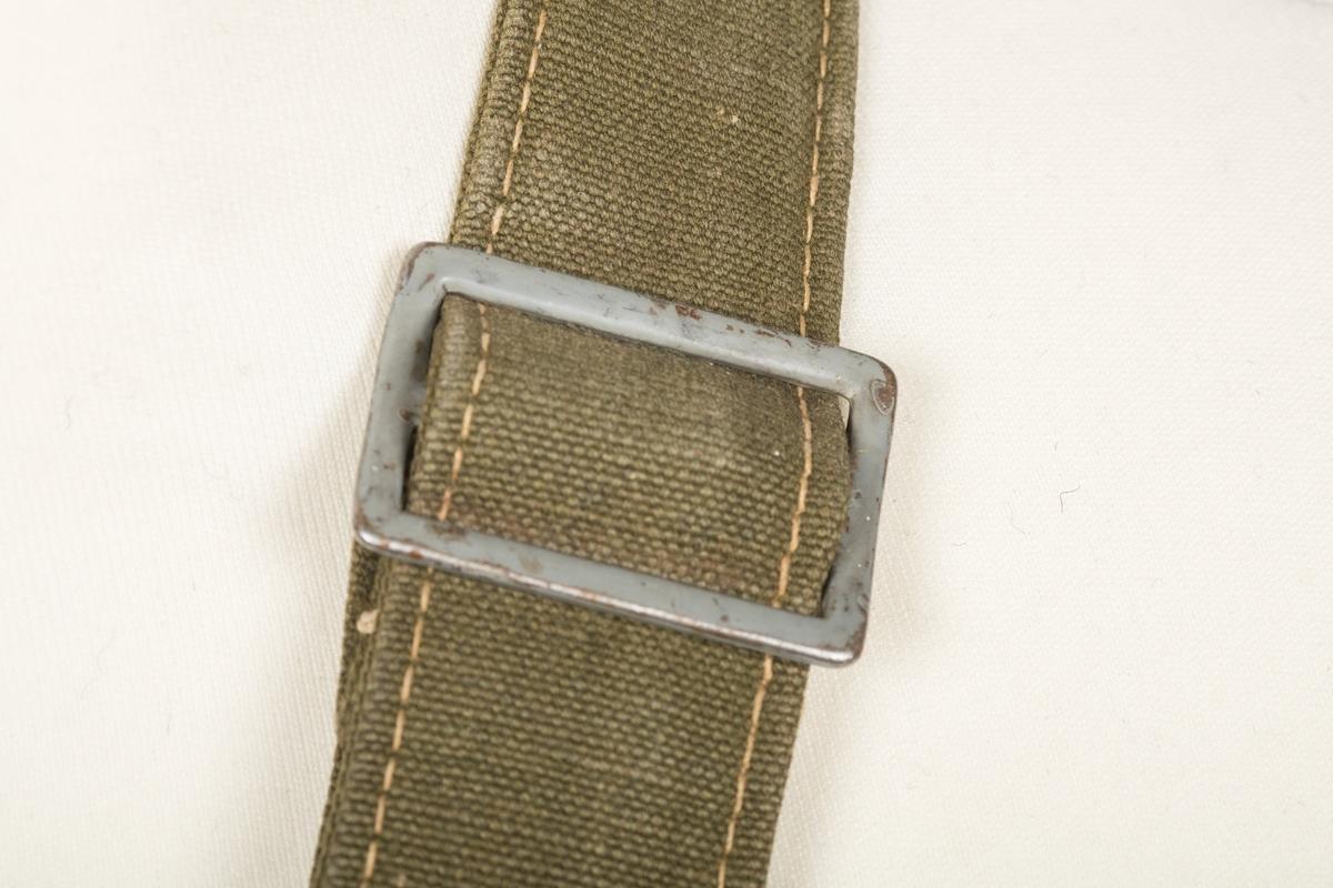 Liten grønn militærveske med skulderrem, to kneppbare skinnforsterkede remmer og metallkrok til oppheng/ feste.