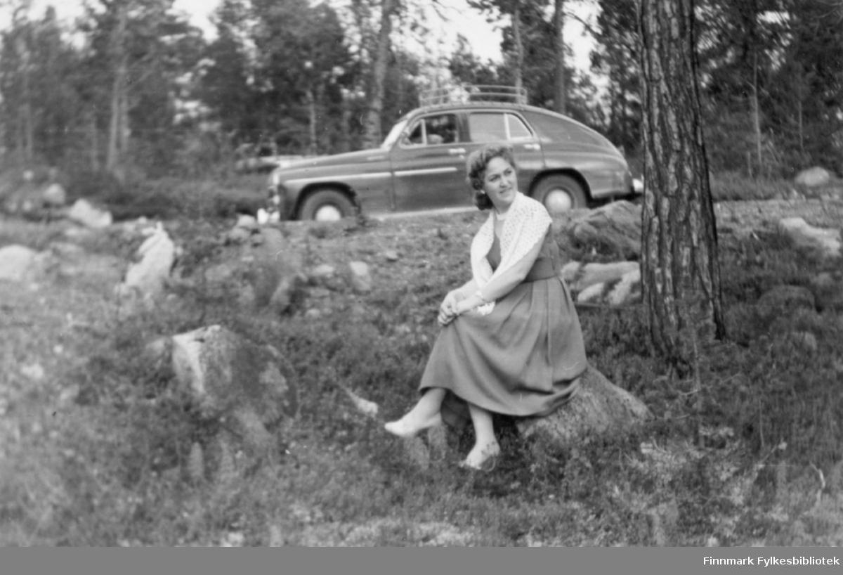 Ester fotografert i skogen på 1950-tallet. En bil, russisk Popeda eller tilsvarende polsk Warsawa (1954-1957) står i bakgrunnen. Familiealbum tilhørende familien Klemetsen. Utlånt av Trygve Klemetsen. Periode: 1930-1960.