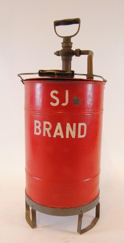 """Handspruta med cylinderformad vattenbehållare på tre fötter. Vattenbehållaren är rödmålad med """"SJ BRAND"""" i vitt. Handtag upptill på pump. Sprutmunstycken sitter fast i pumpen. När handsprutan pumpas går det att hålla fast handsprutan genom att ställa en fot på en av behållarens fötter. Bärhandtaget är fastsatt i två öglor i behållarens överkant."""