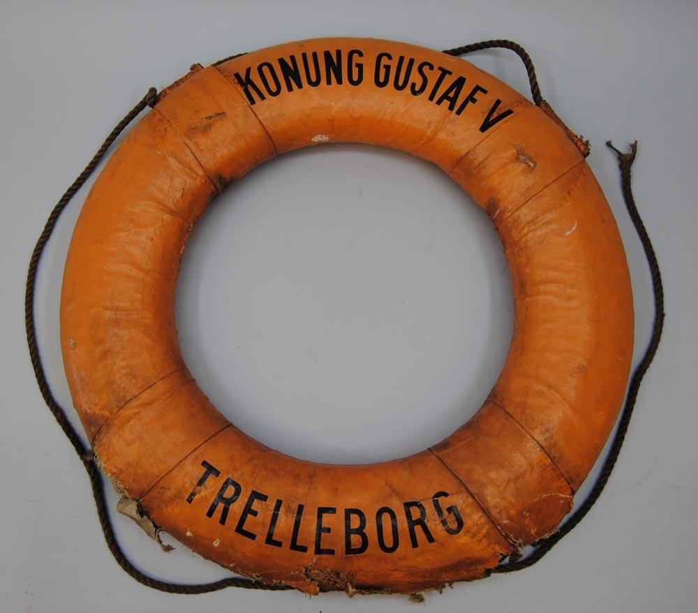 """Livboj av kork klädd med orange målat tyg. På framsidan står det """"KONUNG GUSTAF V"""" upptill och """"TRELLEBORG"""" nedtill med svart schablonmålad text. Bojen har ett rep som är fäst på utsidan."""