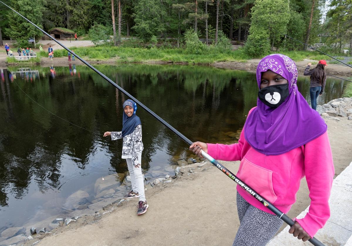 Fra temadagsarrangementet «Skog og vann - naturskole for alle!» på Norsk skogmuseum i Elverum i juni 2018.  Fotografiet er tatt på ved fiskedammen på sørenden av Prestøya, der en del av de tilreisende skoleelevene prøvde fiskestenger.  Enkelte fikk også fisk.  Her er det to jenter med hudfarge og hodebekledning (hijab/nikab) som tyder på at de hadde familiebakgrunn fra sørligere himmelstrøk som har latt seg avbilde med fiskeutstyret.  «Skog og vann» var ett av femten temadagsopplegg Norsk skogmuseum tilbød barnehager og grunnskoler i 2018.  De fjorten andre hadde mer avgrenset tematikk, og mange av dem var orientert mot årstidsspesifikke forhold i naturen eller i tradisjonelt arbeidsliv.  «Skog og vann» var derimot tilpasset de mange som ønsket en elevtur til museet mot slutten av skoleåret, uten noe spesielt læreplanrelatert pedagogisk mål.  Aktivitetstilbudet var derfor vidtfavnende og mangfoldig, fordelt på et stort antall «stasjoner» med aktivitetstilbud på museets uteområde.  Aktører fra en del frivillige organisasjoner med skog- og utmarksarktiviteter på programmet samarbeidet med museets formidlere om avviklinga av arrangementet.  I 2018 samlet «Skog og vann» 3 000 elever fordelt på fem dager.