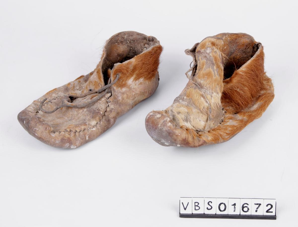 Ett par skinnsko. Hårsiden ut, med pels. Skoene består av fire deler, en såle, en del som dekker vrist og to deler med midtsøm vertikalt på hælen. Alle delene er sydd sammen med grov tråd. Snorer bindes over vristdelen, for å snøre skoen fast på foten. Rester av halm på innsiden av skoene.