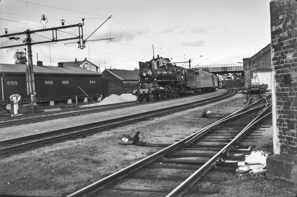 Persontog fra Trondheim til Oslo Ø over Røros, Pt. 302, kjører inn på Hamar stasjon. Toget trekkes av damplokomotiv type 26b nr. 229.