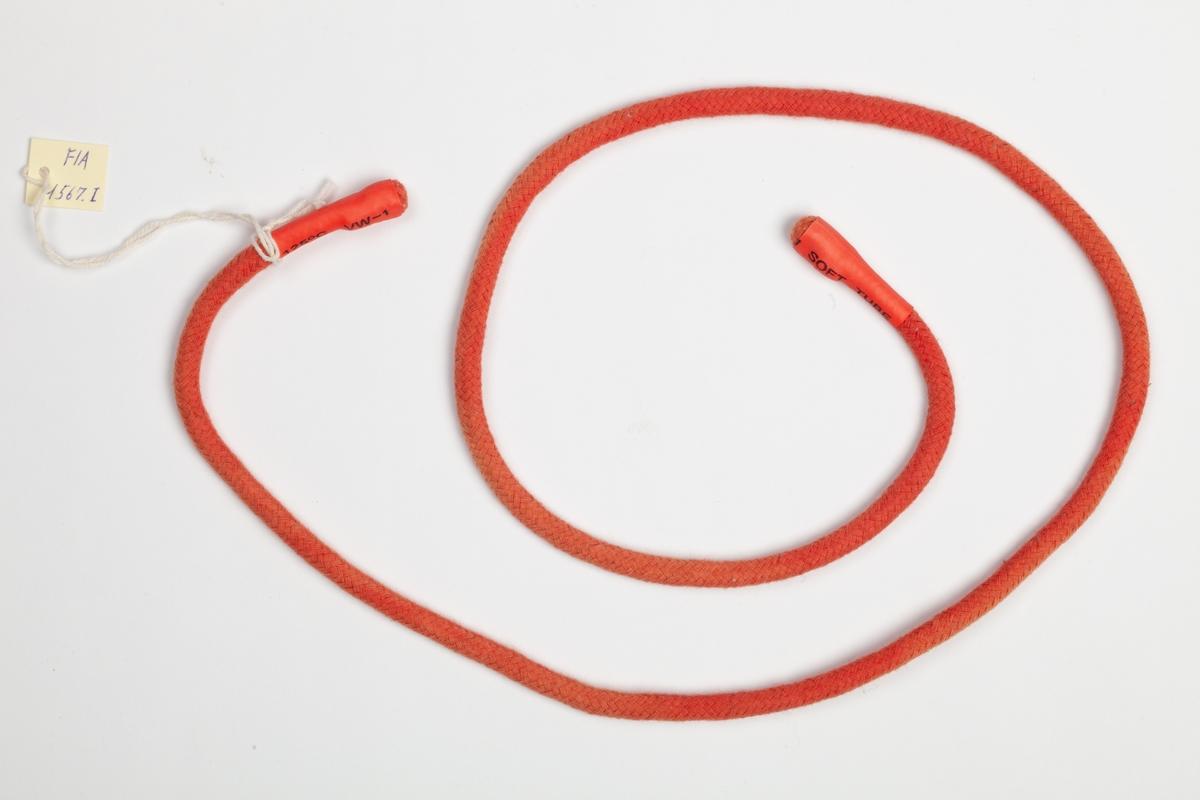 En rundvevet rød smal rem med gummiender. Turnikèen kan snøres sammen om et lem ved livstruende skade eller huggormbit.
