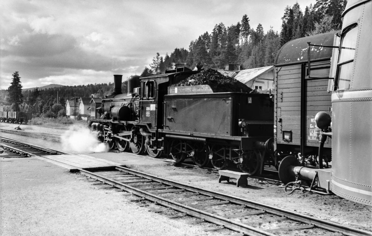 Rena stasjon med godstog retning Hamar i spor 2 og persontog retning Hamar, tog 374, i spor 1. Godstoget trekkes av damplokomotiv type 18c nr. 226.