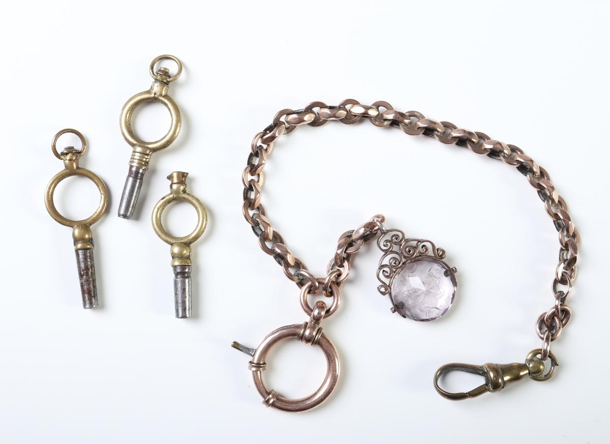 Genombruten, förkopprad urkedja med tre urnycklar, samt en berlock av glas med en graverad romersk soldat på ena sidan.  Inskrivet i huvudkatalog 2017.