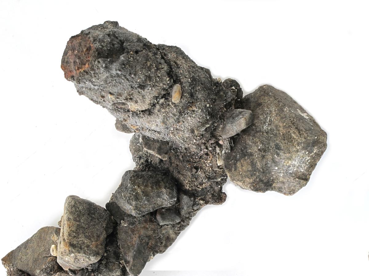 Korrosjonklump d)  Korrosjonsklump omkring et vinkelbøyd jernstykke. Består av jern og rust, stein og sand som drysser.