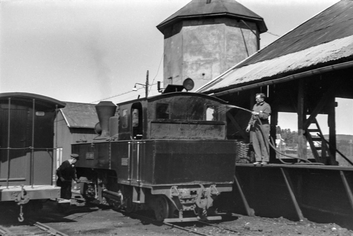 Kullfylling og spyling av kullene for å unngå støv på damplokomotiv nr. 6 HØLAND på Bjørkelangen stasjon. Lokomotivet ble benyttet i blandet tog fra Skulerud til Sørusamd.