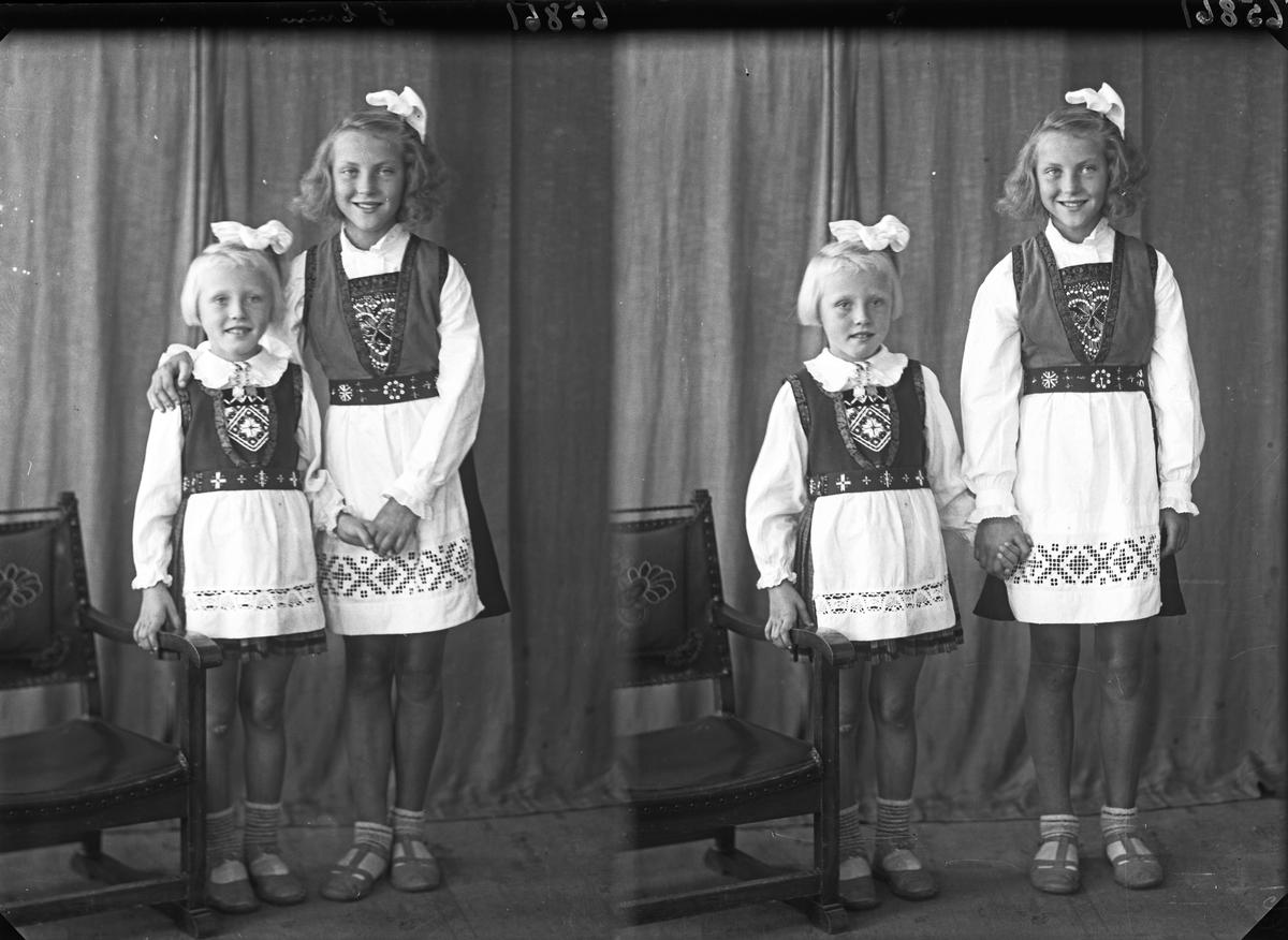 Gruppebilde. Familiegruppe på to. To unge piker i nasjonaldrakt med sløyfer i håret. Søstre. Bestilt av Erling Nilsen. Strangt. 181