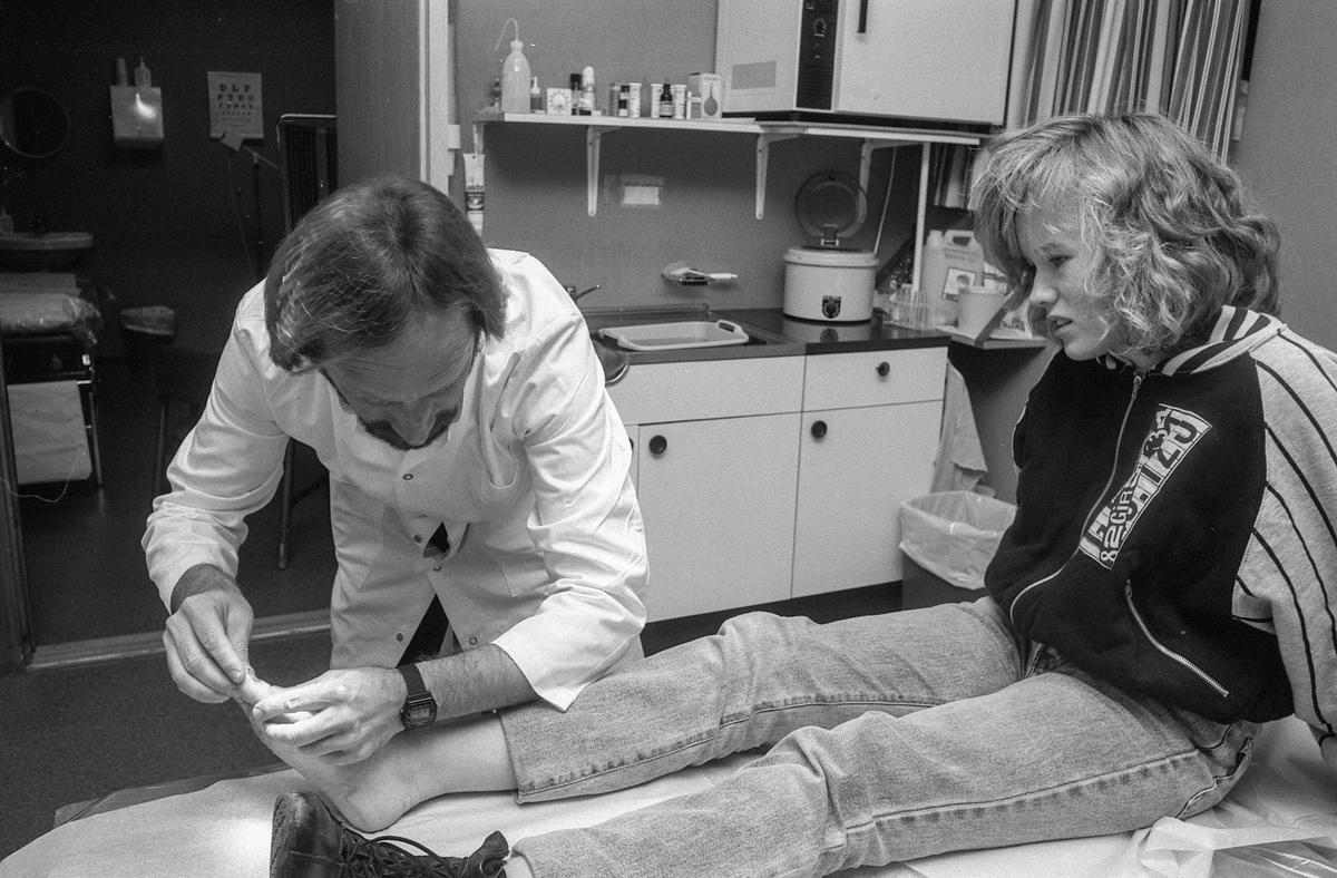 Ski legevakt, jente på undersøkelsesbenk med vond tå. Blir undersøkt av legen.