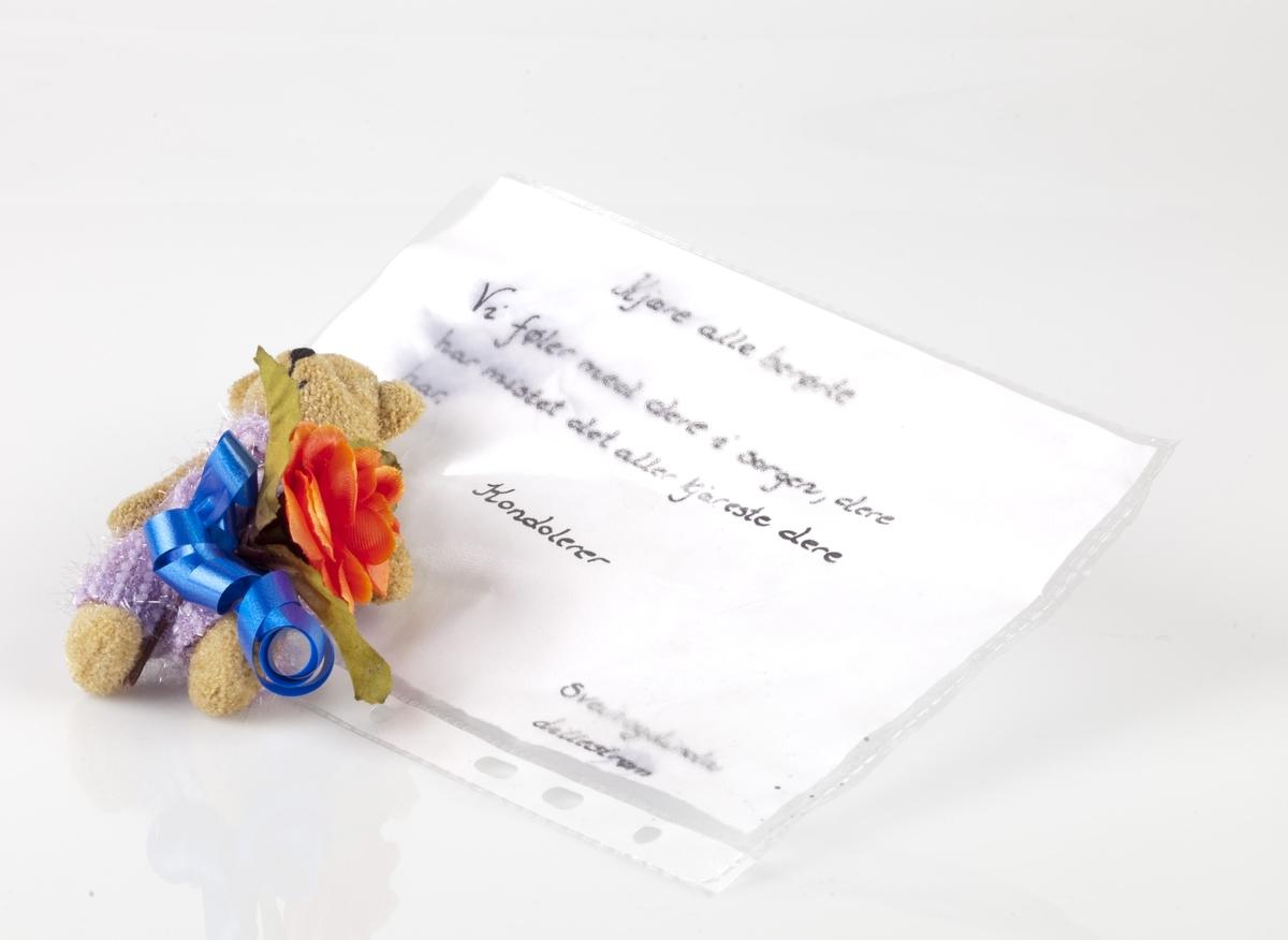 """Tøybamse med hilsen innsamlet etter terrorhandlingen 22. juli 2011 fra minnesmarkeringene Lillestrøm.   A: Dette er en liten lysebrun bamse med lilla/fiolett strikkebukse, bukseseler og sløyfe i halsen. Klærne har metalliske, skinnende tråder i strikken, og bukseselene er festet med to knapper av tre. Rundt livet på bamsen er det knyttet et blått gavebånd med krøller og til den er det festet en rød/oransje plastrose med tre blader. Gavebåndet er fortrinnsvis brukt til å feste bamsen til hilsenen (B). B: Hilsenen er skrevet med sort tusj på en hvitt papirark og ligger i en A5 plastlomme med rygg som gjør at den kan settes i perm. Skriften er noe """"utflytende"""" etter kontakt med vann."""
