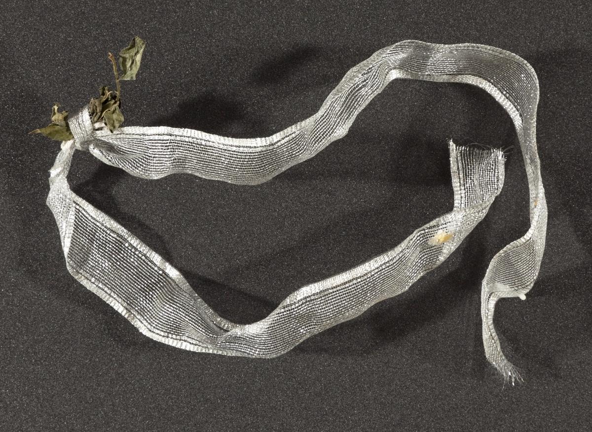 Sløyfebånd innsamlet etter terrorhandlingen 22. juli 2011 fra minnesmarkeringene i Lillestrøm.   Vevet sløyfebånd i sølvfargede tråder. Båndet inneholder metalltråder, spesifikt i kantene som gjør at sløyfen kan formes. Rester av en tørr rose er igjen i en knute omtrent på midten av båndet. Sløyfen er gjennomsiktig og ikke rettet ut. Det er noe rester av stearin og og andre udefinerbare substanser etter utendørs oppbevaring.