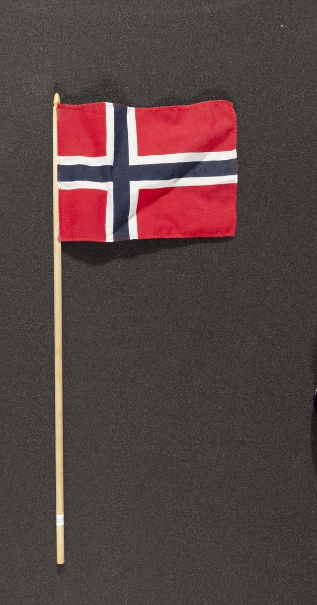 """Flagg innsamlet etter terrorhandlingen 22. juli 2011 fra minnesmarkeringene i Lillestrøm.   Klassisk norsk flagg slik vi kjenner det fra 17.mai feiringer: Blått kors i midten, hvitt kors som """"omkranser"""" det blå (litt tynnere fargefelt) på en rød bakgrunn, de blå og hvite korsene går helt til kanten av flagget. Dimensjonene på feltene er slik at de to røde felten mot pinnen er halvparten så store som de to ytterste røde feltene. Sømmene er sydd med rød tråd. Flagget brukes av både barn og voksne.  Selve flagget er litt skrukkete men pinnen er ren og ikke slitt. Det er et klistremerke med navnet på produsenten nesten nederst på pinnen. Den er hvit med sort skrift og en tegnet hund."""
