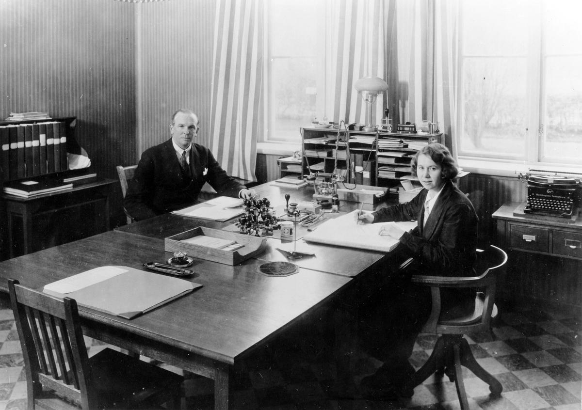 Kontorsrum med en man och en kvinna på var sin sida av ett större skrivbord. Inifrån Alingsås lasarett.