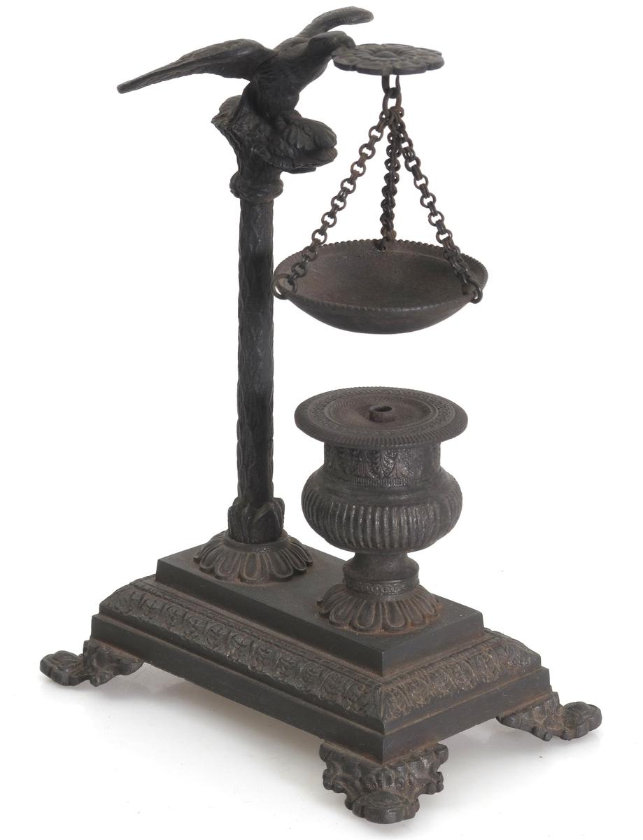 Kvadratisk fot på fire ben. Søyle med en ørn på toppen, som holder  en rosett med en liten skål i lenke. Under skålen en urneformet oljebeholder med løst flatt lokk.