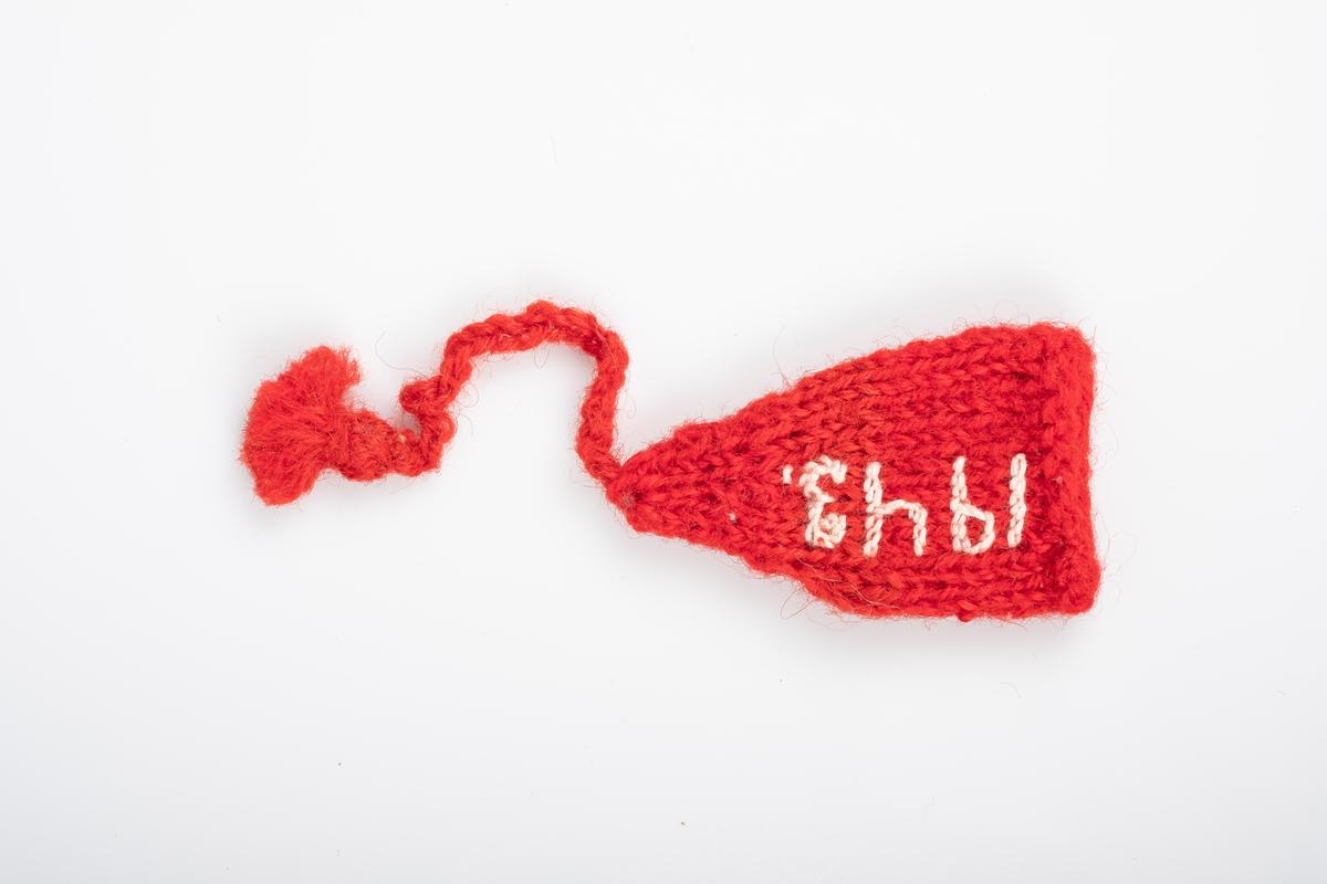 """En liten rød strikket lue med en dusk. Det er brodert """"Grini"""" og """"1943"""" på luen. Luen ligner en nisselue."""