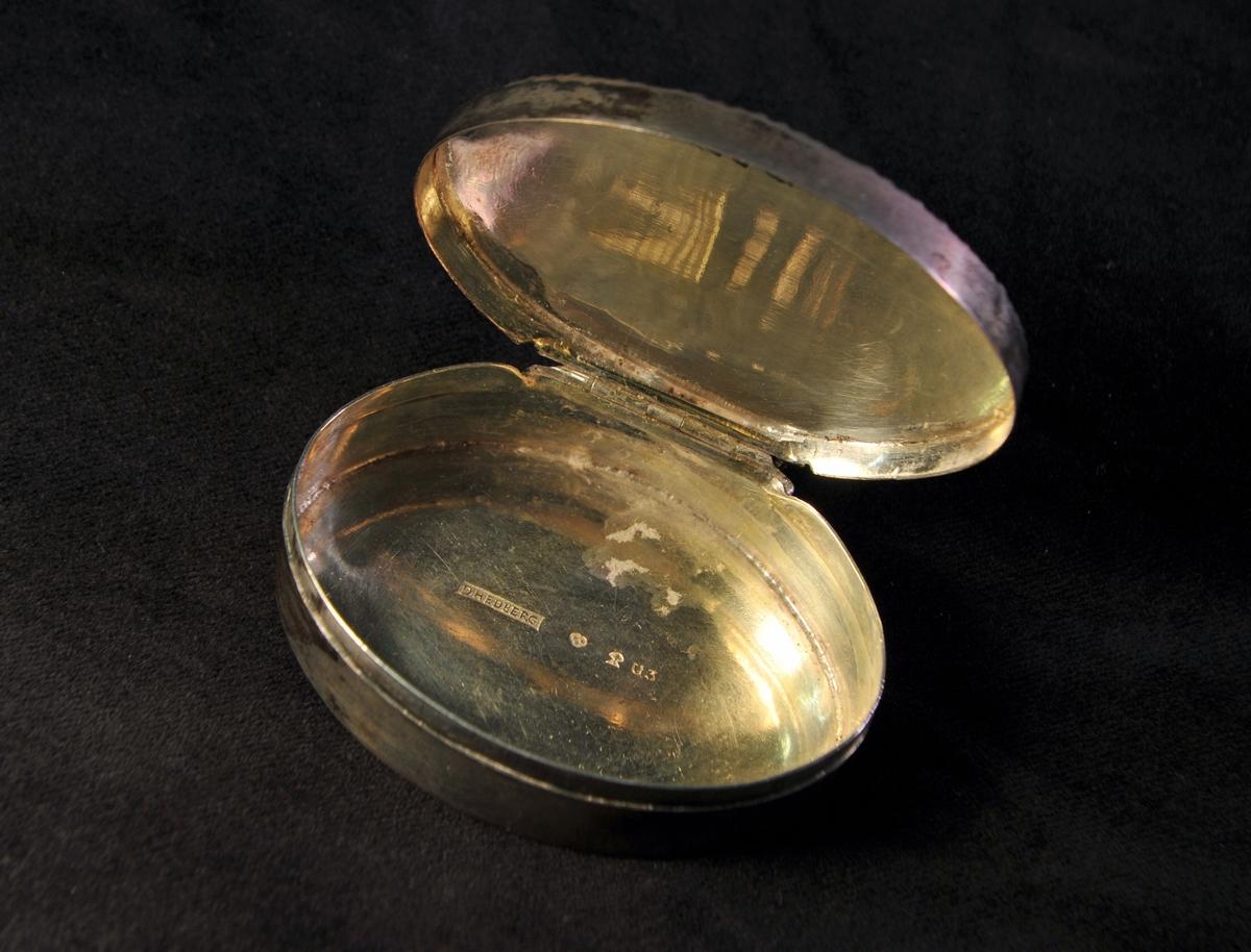 En oval dosa av silver.Locket är prytt med filigranarbete och infattade, slipade glasstenar (8 st.) i rött. Allmogestil.Stämplad invändigt i botten.