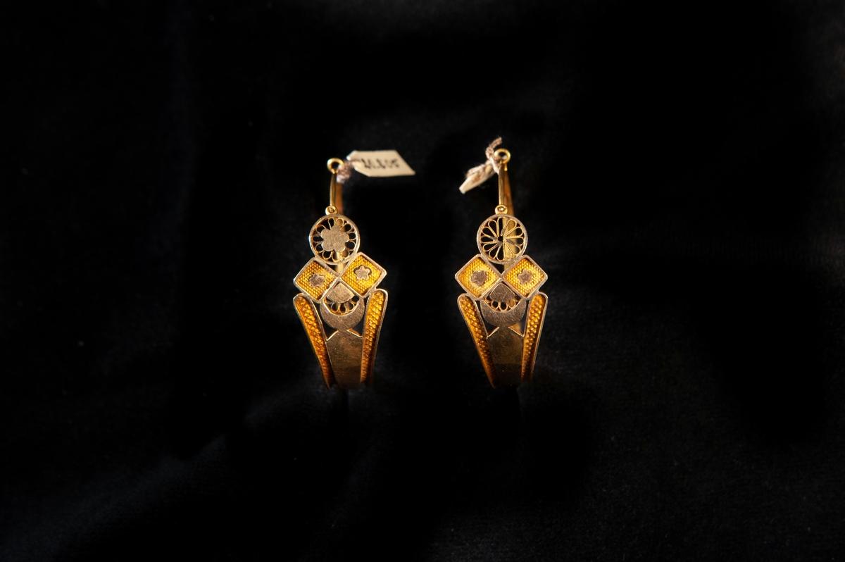 """Örhängen av guld, delvis i filigranarbete. Dekor i form av fyrpass, blommor m.m. Graverade initialer inuti: """"H.C.A.D."""". Stämplad utanpå längs skenan (mycket otydlig årsstämpel)."""