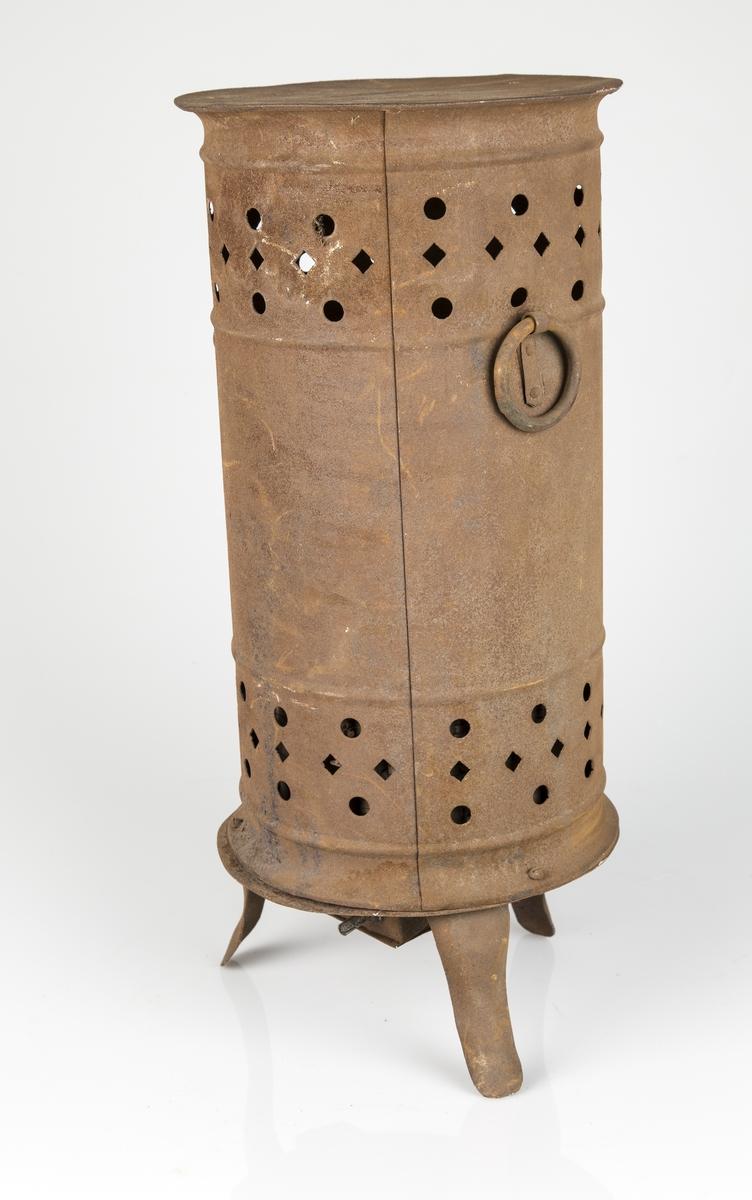 Høy sylinderformet frittstående varmeovn. Stansede luftspalter oppe og nede på ovnen. To runde håndtak og tre ben. Strømkabelen mangler,