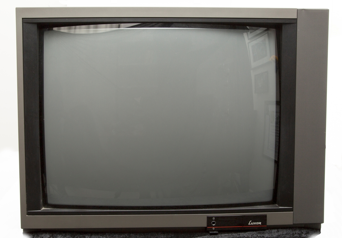 Fjernsynsapparat. Mellomstor bordmodell. Høyttaler på siden. El-kabel.