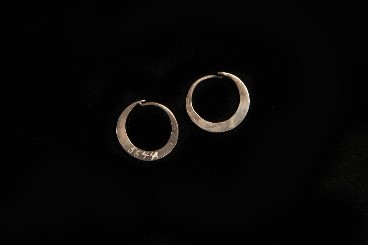 En rund örring av silver. Platt, enkel modell. Hör ihop med JM.5644:2.