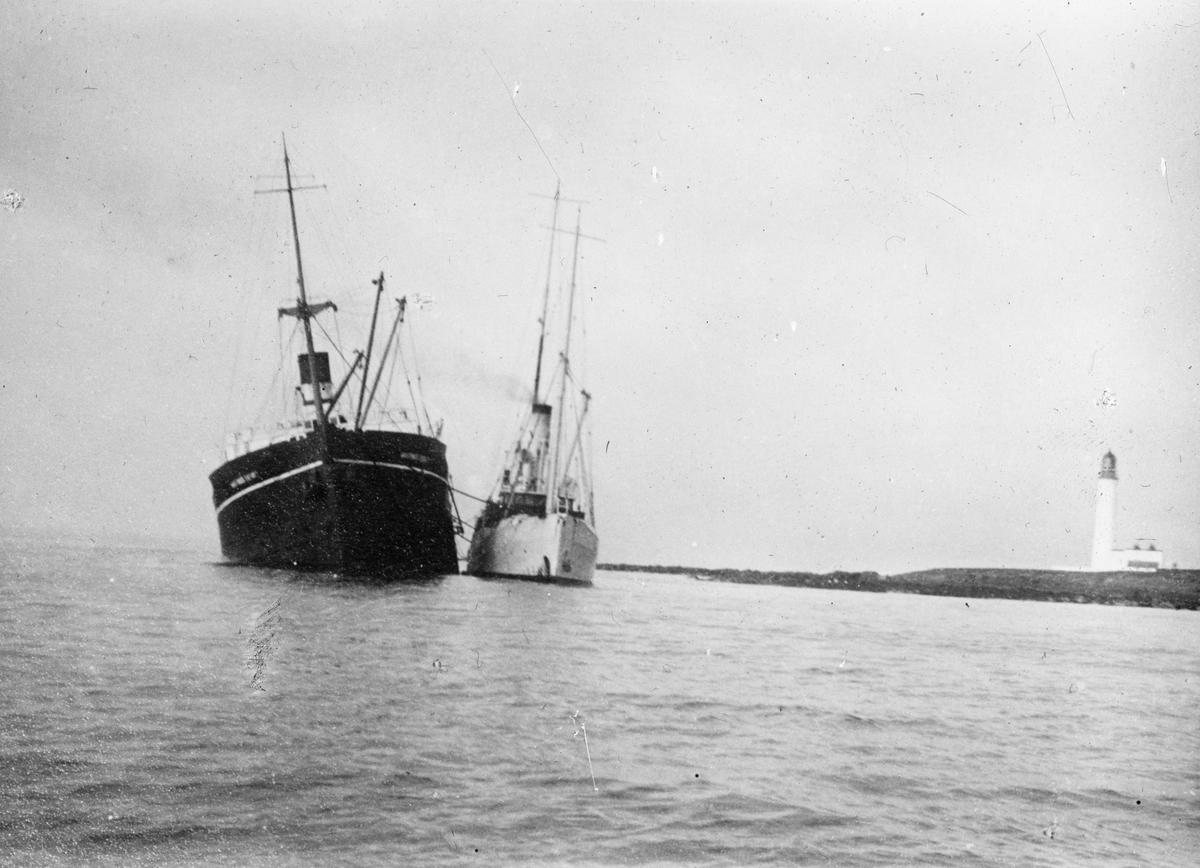 To dampskip i kystlandskap, til høyre i motivet et fyrtårn. Fartøyet til venstre i motivet har slagside.