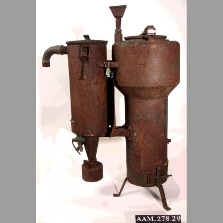 Gassgenerator brukt på sjekte. Ble drevet med trekull. To sylindere forbundet m.stag. Trefot under en av dem. Lokk på b. Etikett for produsent festet på, såvidt lesbar.