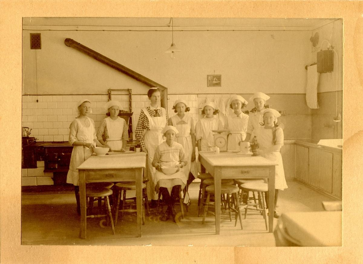 En grupp flickor undervisas i skolköket på Centralskolan. I mitten står lärarinnan Elsa Broman.