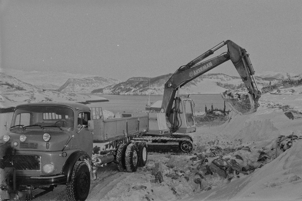 Leirfjord, Sundøy. Arbeidet er i gang på ferjeleiet på Sundøy. Gravemaskin og lastebil på veien ned til Sundvågen. Finnes som VBH.F.2010-102-0017 Bildet er brukt i Leirfjordkalenderen - april 2016