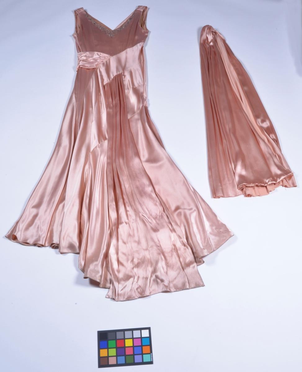 Lång festklänning av rosa satinsiden. Broderad med pärlor och strass runt den v-formade halsringningen. Utan ärm. Sjal i samma tyg hör till.