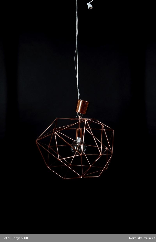 """Taklampa för elektrisk belysning. Stomme av metallstänger i koppar monterade i assymetriska trianglar i en genombruten, närmast rund form. Inuti lampan cylindriskt fäste för lampsockel i koppar och stor klar rund halogenlampa. Halogenlampan väl synlig på grund av/tack vare den glesa, genombrutna skärmen och är en del av formgivningen och lampans helhetsintryck. 3 halogenlampor i 18W=25W medföljer, en monterad i lampan, två i kartonger märkta """"globen lighting"""" (NM.0332259A-B och NM.0332260A-B). Upphäng av tvinnad metalltråd, lampsladd trädd genom smalt rör av klarplast. Cylindrisk takkopp av koppar. /Maria Maxén 2016-01-21"""