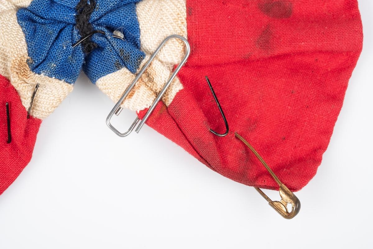 Sløyfe av tekstil i rødt, hvitt og blått. På midten av sløyfen er det påsydd en metallknapp med Den norske løven på. Det er påfestet svart ståltråd bak, trolig for å brukes til festing på klær. Det er også en binders og sikkerhetsnål på sløyfen.
