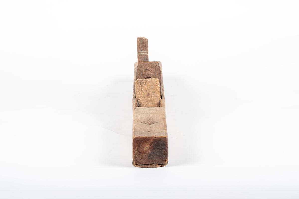 Høvelklossen er lang og kraftig. Den har et pent utskåret håndtak bak høveljernet. Under selve høvelklossen er det festet på en tynn planke som dekker undersiden, og på oversiden av klossen (foran høveljernet) stikker det gjennom en trekile, som er formet som en firkant. Det ser også ut til å være felt inn en liten treplate mellom planken og stokken, akkurat foran åpningen til høveljernet under. Det er et skruehull oppå klossen.