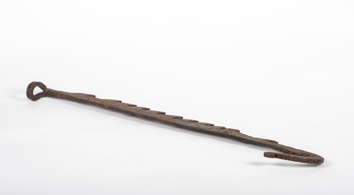 Lang, flat og taggete med ring i ene enden og krok i andre enden.