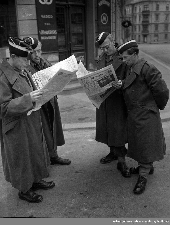 Fire soldater leser Arbeiderbladet på gata i Oslo. Bilde tatt i forbindelse med Stortingsvalget 12. oktober 1949.