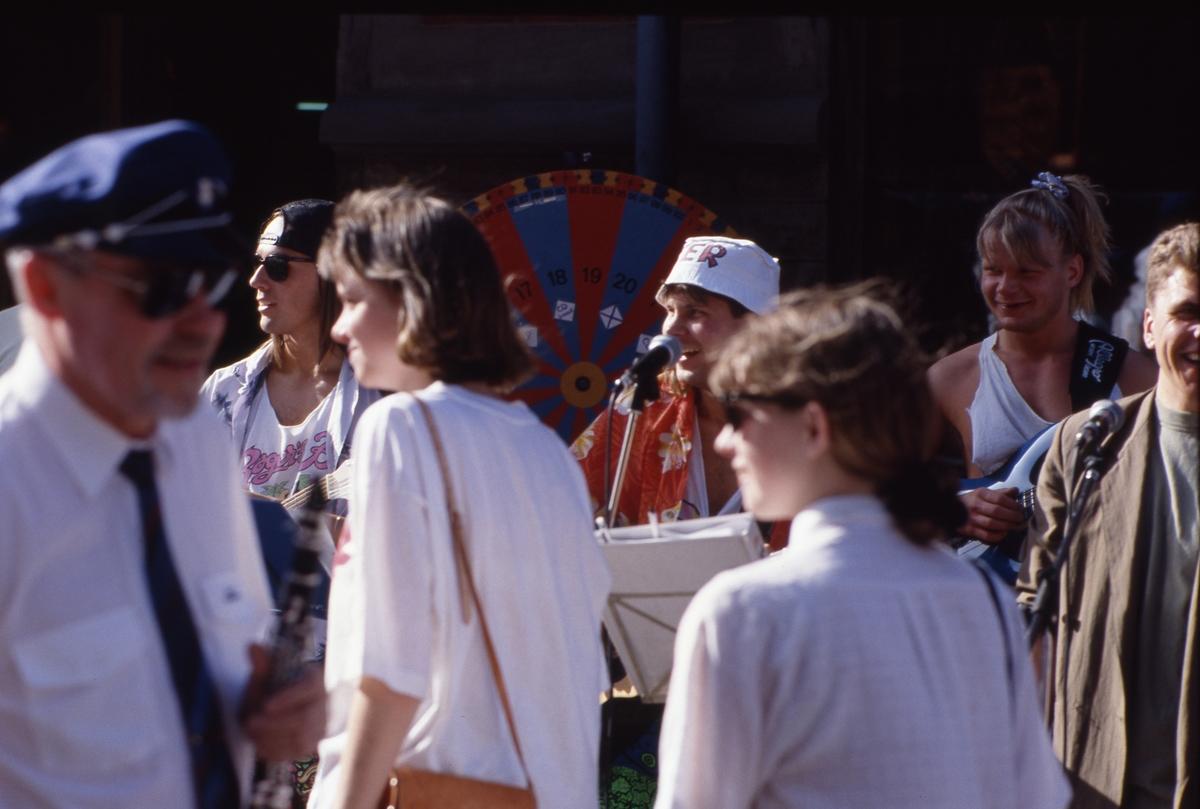 Det är troligtvis Karneval i stan. (Arbogakarnevalen hölls första gången 1992). Bröderna Peter Gustavsson och Magnus Gustavsson spelar gitarr på stan. Till höger ses halva sångaren, Marcus Olsson. Den suddige mannen i förgrunden är Håkan Harrysson, dirigent för Arboga Blåsorkester.