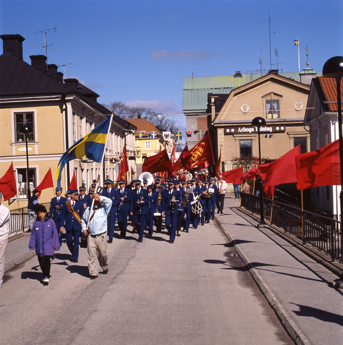 Första maj. Demonstrationståg med röda fanor och plakat. Först går ett par med en svensk flagga. Sedan följer Arboga Blåsorkester under ledning av Håkan Harrysson. I bakgrunden ses kvarteret Stadsgården till vänster och Kungsgården till höger. Kapellbron är dekorerad med röda fanor. Socialdemokrater demonstrerar.
