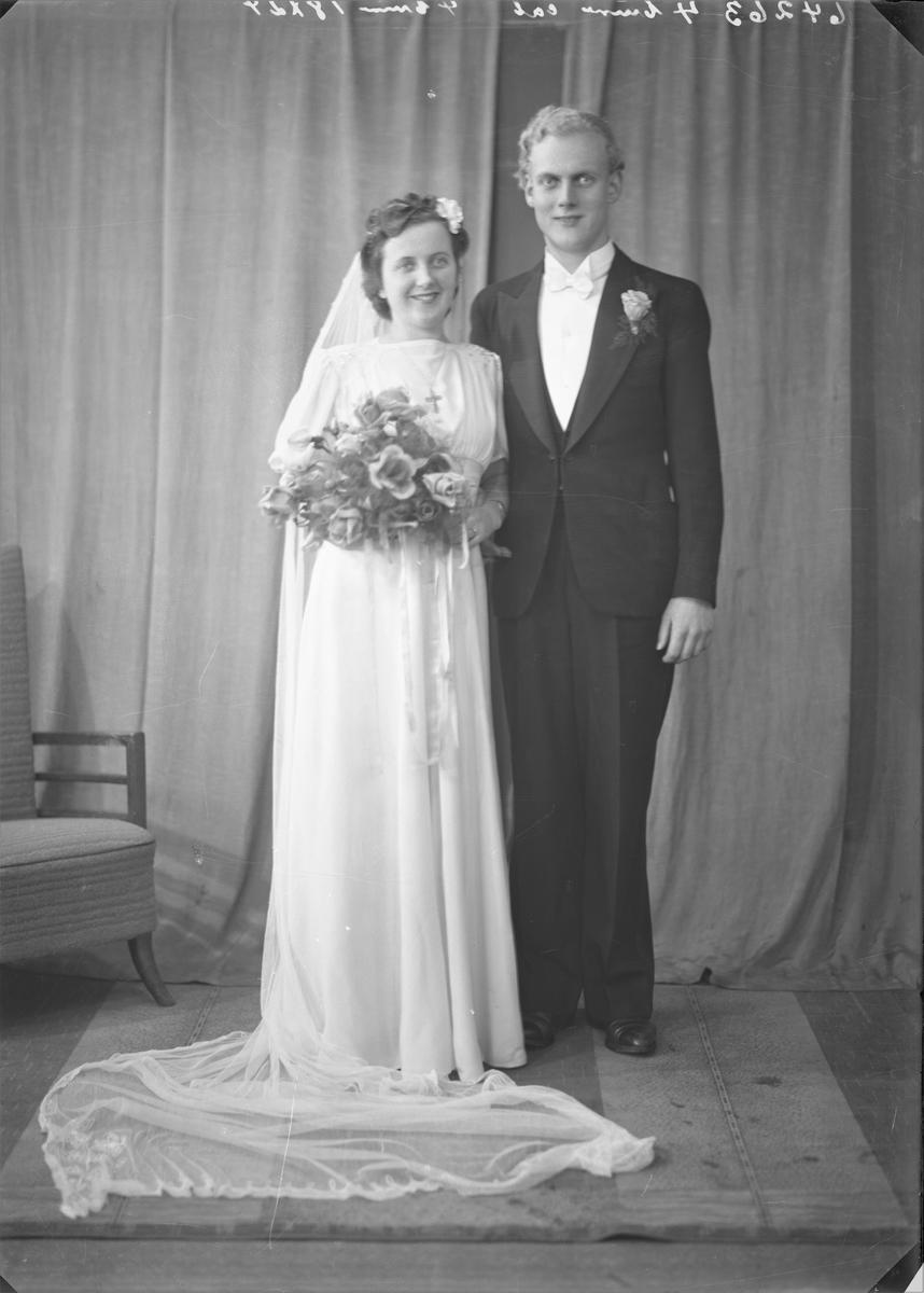 Gruppebilde. Brudebilde. Ung mørkhåret kvinne i lang hvit brudekjole, blomsterbukett i hendene. Ung lyshåret mann i mørk smoking med hvit skjorte og hvit sløyfe. Brudepar. Bestilt av Finn Trondsen.