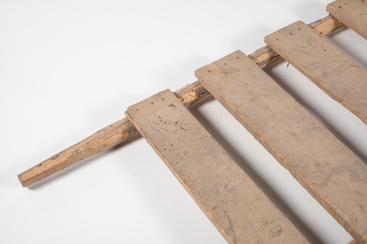 Rektangulær båre, brukt til å bære slaktegris. Består av 8 planker lagt på tvers og spikret fast til to trestenger. Det er rester av bark på stengene, og endene som er håndtak er spikket til for bedre grep.
