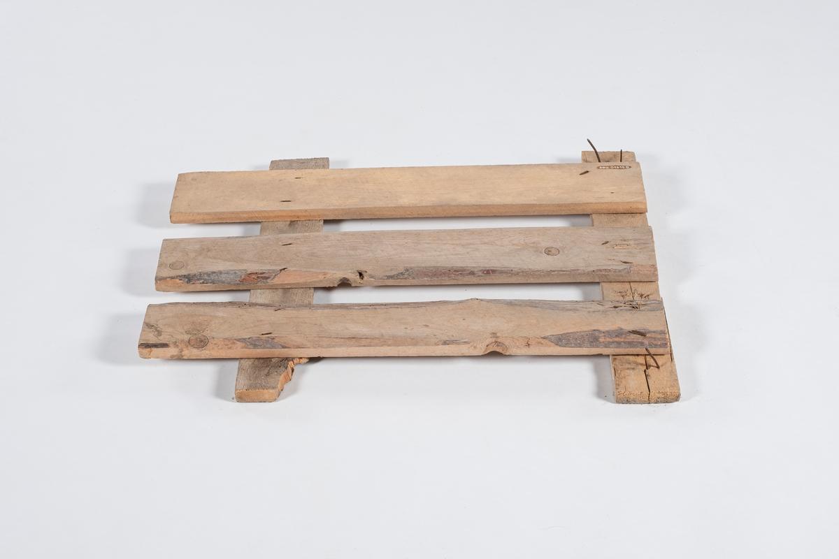 Løs vegg til grisekasse for transport av gris. Veggen er i tre, og er satt sammen av 5 planker. Veggen er ikke tett, det er litt mellomrom mellom plankene.