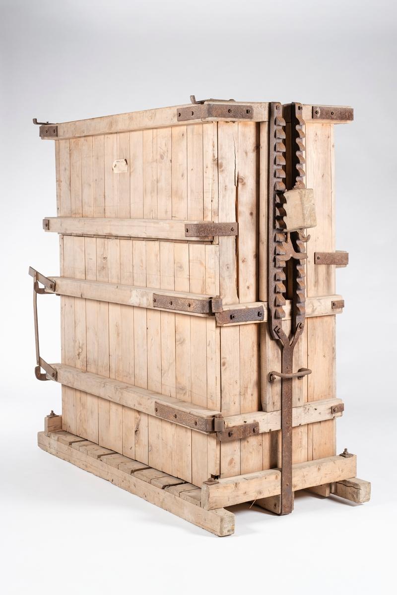 Kassen er av tre, og har ilegg ovenfra. I den ene langsiden er det en hengslet dør før for uttak av høyballen. Det er smidd jernbeslag i alle kassens hjørner. I kassen er det fire åpninger i bunnen og i bakre vegg for plassering av pressetrådene. På hver kortside av kassen er det en åpning for tverrstokken til lokket. På hver side av åpningene er det en tannrekke for presstengene og festing av lokket. Under tannrekkene er det et håndtak. I begge hjørnene på fremsiden er det kroker.