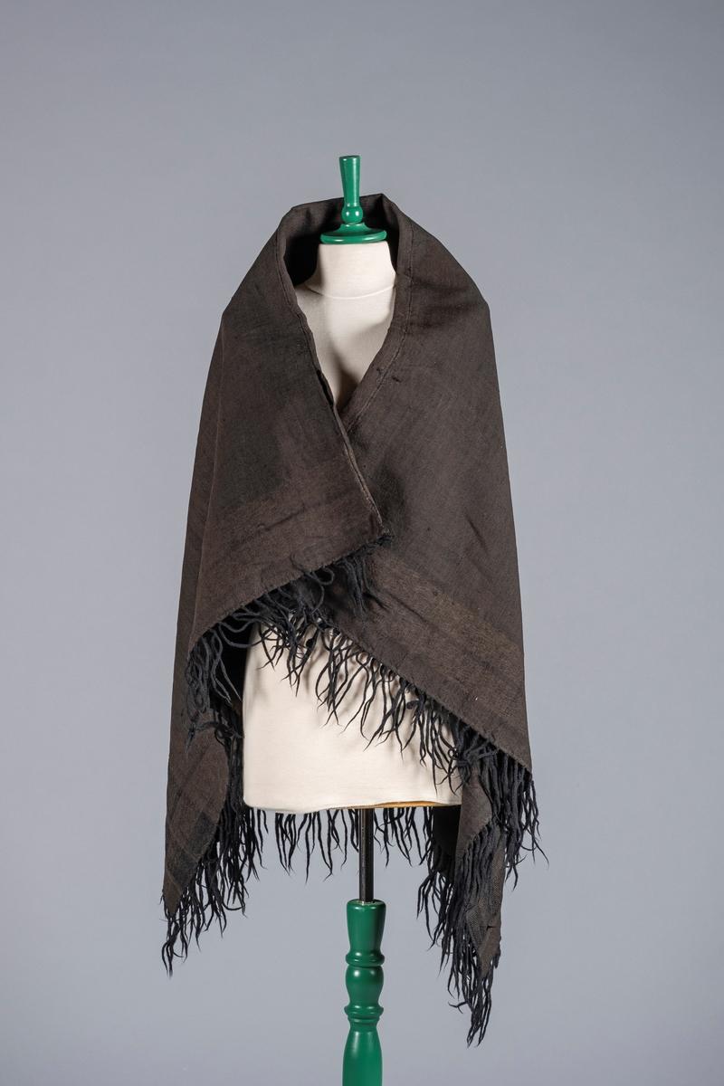 Sort sjal sydd sammen av to deler. Det er frynser i kantene. Sjalet har mønster av to brede striper langs kantene.
