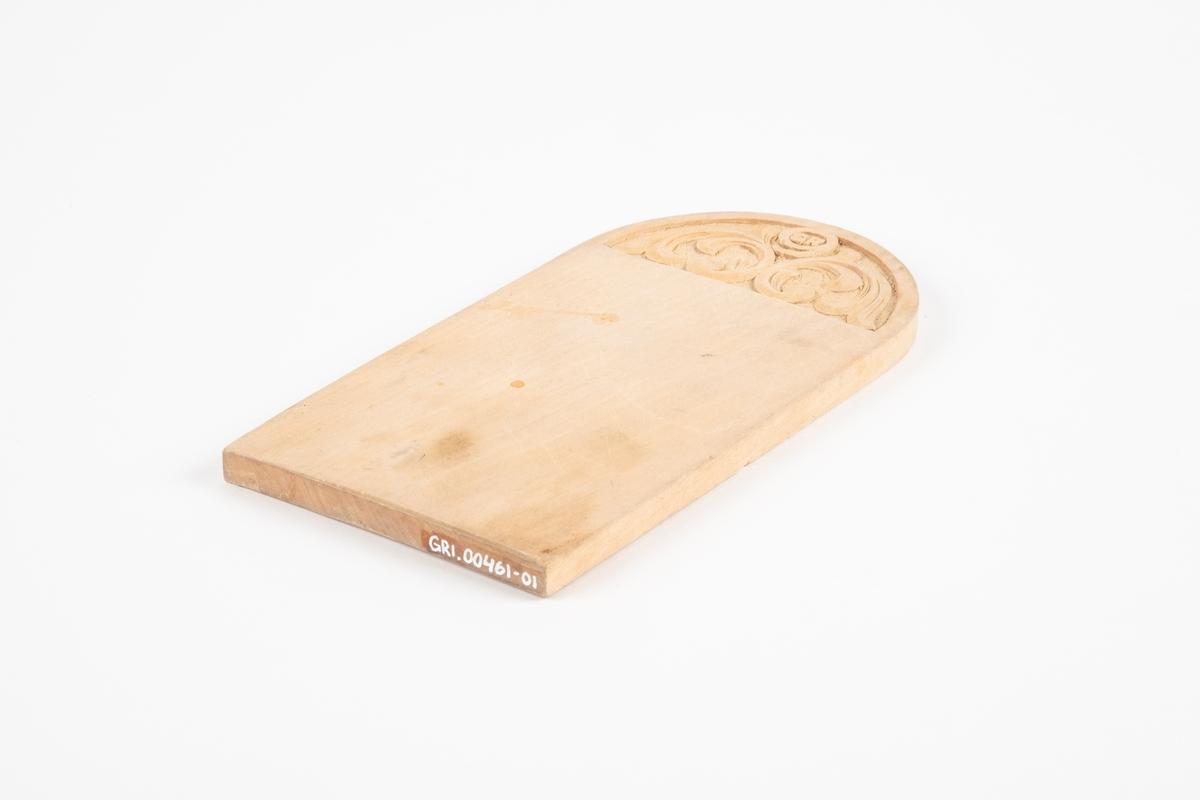Trefjøl med bue i den ene enden. Den har utskjæring av Grini-symbolet og akantus.