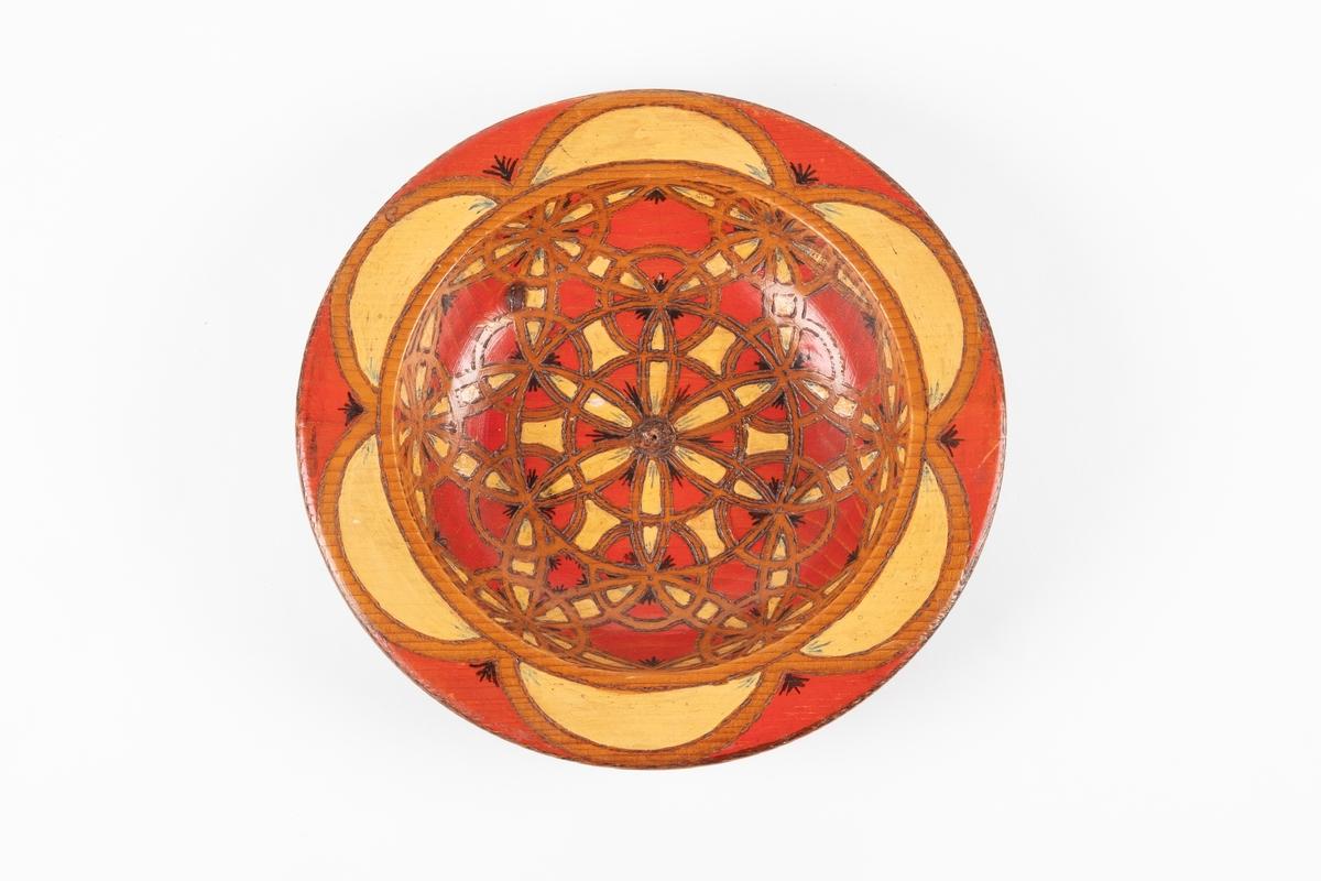 Trebolle med innbrent mosaikkmønster. Bollen er i rødt og gult på oversiden og brunt på undersiden. Det er påført tekst på undersiden.