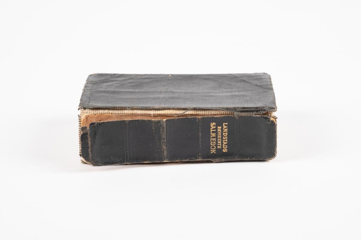 En salmebok med svart omslag av papp og tekstil. De siste sidene i boken består av signaturer.