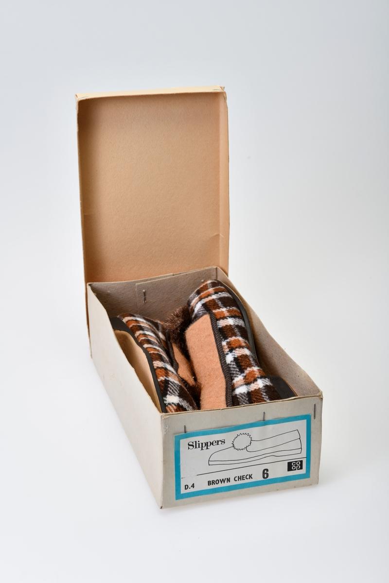 Rutede stoff tøfler med gummisåle. Nedbrettede sider og dusk oppe på risten. Merkelapp inne i tøffelen. Tekst på siden av sålen. Disse oppbevares i en skoeske med tekst. Eksen er stiftet sammen i hjørnene.