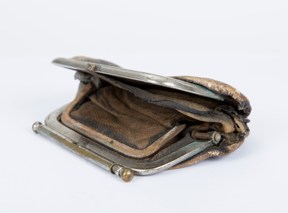 Portemoné, pengepung, skinnpose med metall lukking. Låsen har en stang og en kule på hver ende. Veldig slitt og dårlig i hengslene.