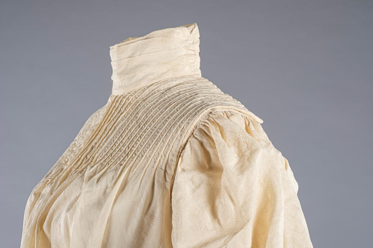 Kremfarget kjoleliv med puffermer og høy hals. Det ytre stoffet er vevd med mønster og foringen er av lin (?). På framsiden er det sydd loddrette brett/ribber. På baksiden er det en metallhekte. Det er metallspiler på innsiden. Det er en liten brystlomme på den indre klaffen. Kjolelivet lukkes først på innsiden og deretter med en ytre klaff på venstre side. Den lukkes med metallhektere. På den ytre klaffen er det et bånd ved nedre kant.