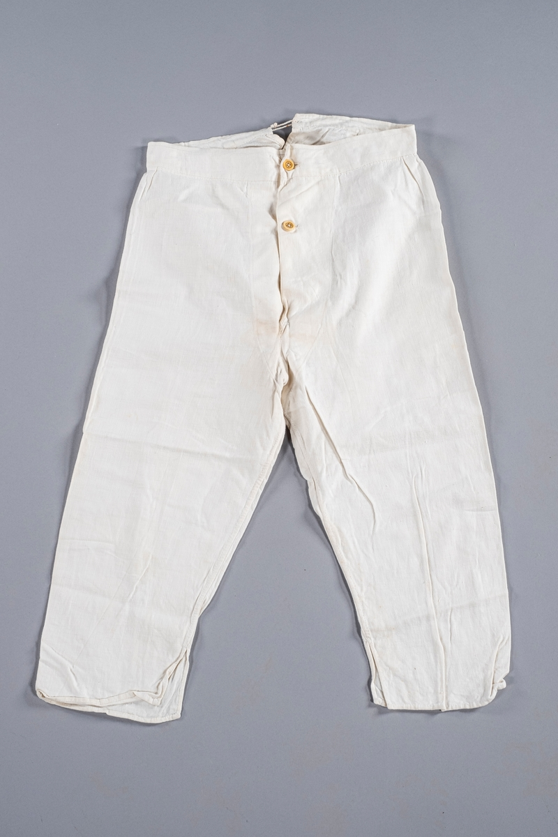 Underbukse i hvit bomull, åpning i front med to knapper, og åpning bak med snøring. Den har folder ved linningen. Nederst i beina er det splitt.