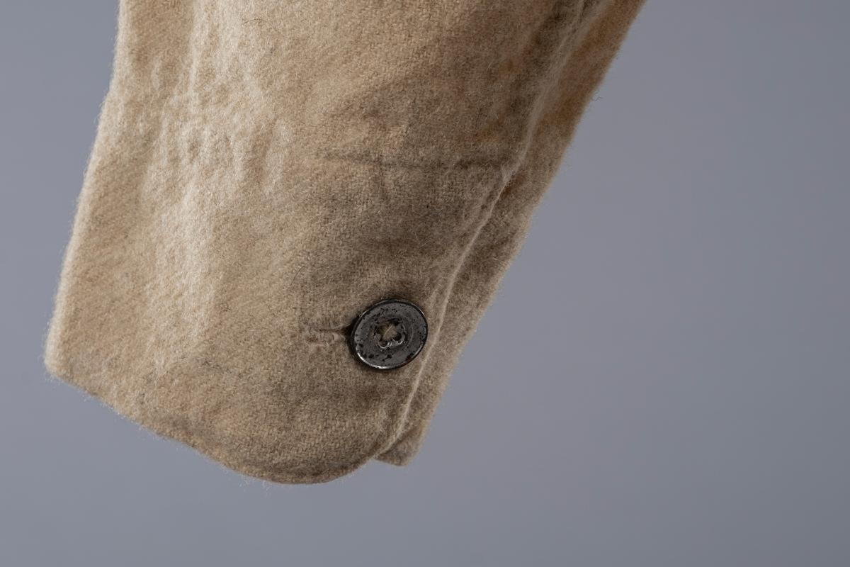 Undertrøye i vadmel med lange ermer og åpning foran med fire knapper. Den ene knappen er trolig av ben og de tre andre er i metall. Det er mansjett med mansjettknapp på ermene. Disse knappene er også i metall. Halsen er rund og uten krage. På høyre side ved nedre kant er det brodert initialer.